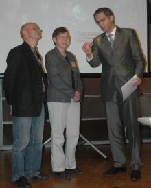 Gerd Hoofe (rechts), Staatssekretär im Bundesjugendministerium überreicht Sabine Ahrens, Stellvetr. Slin, Bildmitte den Preis. Links: Otto Clemens, Geschäftsführer Haus Drei