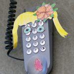 EIn altes Telefon wurde mit Zeichnungen beklebt. Es scheint nun ein Kopf mit Haaren und Augen zu sein.