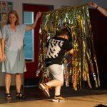 Ein Junge läuft auf einen Vorhang aus goldenen Streifen zu. Zwei Mitarbeiterinnen halten den Vorhang, seine Klassenlehrerin ruft das nächste Kind auf.