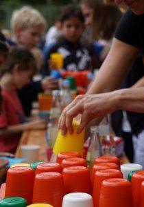 Das Bild zeigt wie eine Hand einen Plastikbecher von einem Stapel Becher nimmt. Im Hintergrund sind Menschen zu sehen, die Getränke bekommen.
