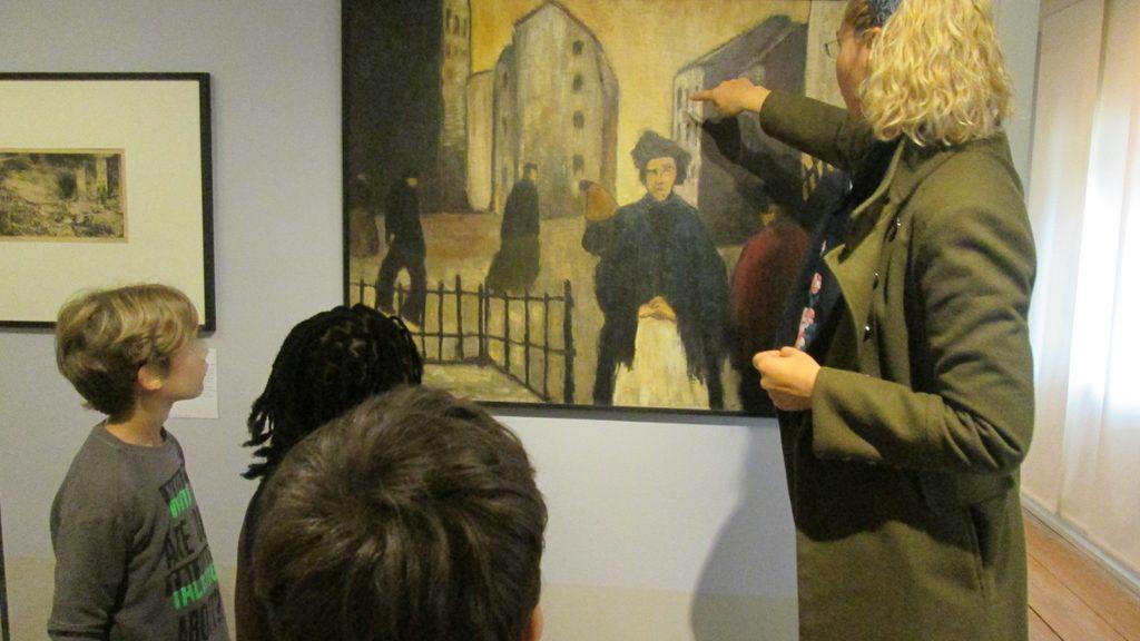 Kinder stehen vor einem Bild und hören sich einen Vortrag darüber an.