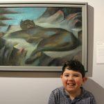 Ein Schüler steht bei einem Gemälde. Es zeigt eine Raubkatze.