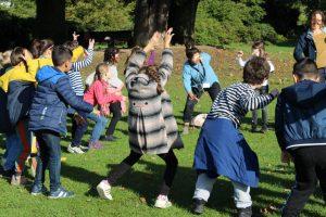 Zusammen mit Künsterlin Meike Klapprodt tanzen Kinder auf einer Wiese.