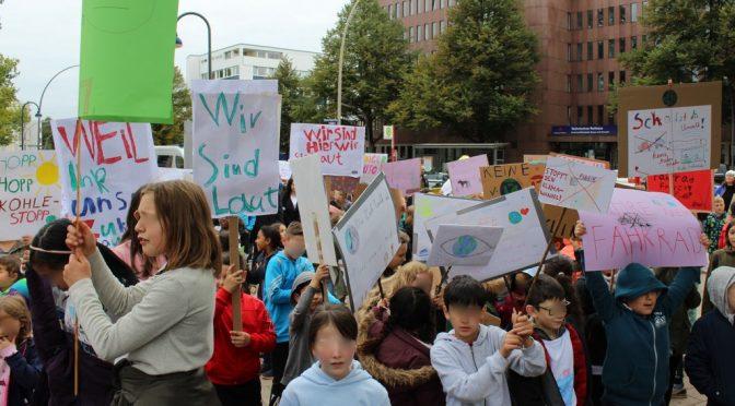 Eine große Gruppe Kinder steht mit Plakaten auf einem Platz.