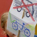 Auf einem Plakat ist ein durchgestrichenes Auto. Darunter ein Fahrrad mit einem grünen Haken.