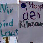 """Man erkennt zwei Plakate. Auf dem linken steht """"Wir sind laut!"""", auf dem rechten """"Stoppt den Klimawandel!""""."""