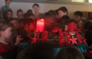 Kinder umringen einen Adventskranz mit einer brennenden ersten Adventkerze.