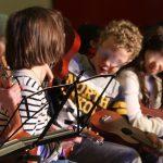 Schüler*innen sitzen zusammen und proben mit ihren Ukulelen.