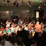 Zu sehen sind die Streicher der 3. Klasse. Im Vordergrund sitzen die Eltern im Publikum. Gino Dirigiert mit dem Rücken zum Publikum.