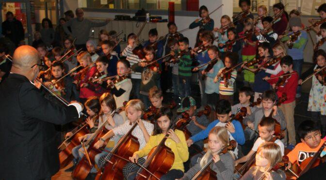 Das Foto zeigt Gino und das Schulorchester bei einem Auftritt in der Aula